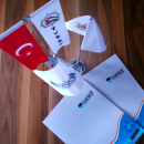 Two boxes with Nasiol logo, Turkish, Tysk, and Nasiol flag stand on the brown wooden surface